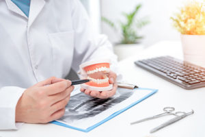 dentist working on a pair of full dentures