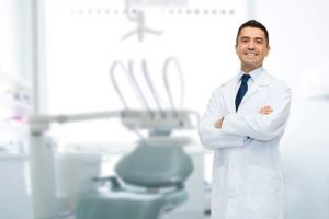 dentist with arms crossed smiling about restorative dentistry